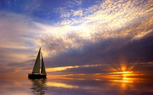 sailboat-in-calm-sea-at-sunset