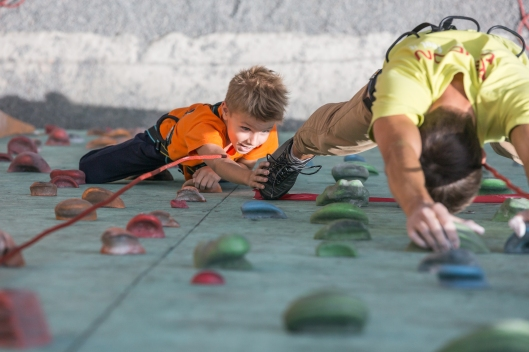 shutterstock_father leading son climbing wall